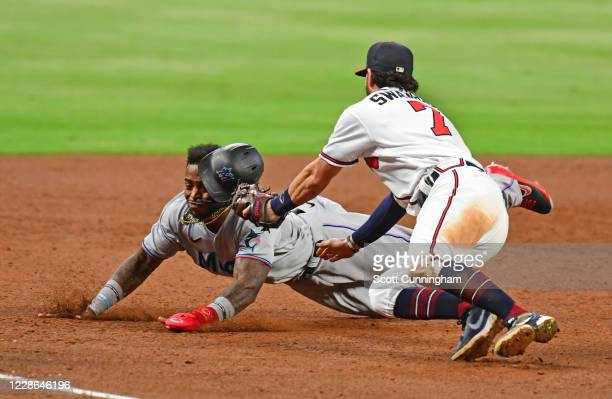 Lewis Brinson of the Miami Marlins is tagged out at third base in the ninth inning by Dansby Swanson of the Atlanta Braves at Truist Park on...