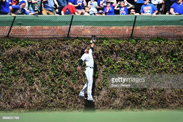 Lewis Brinson of the Miami Marlins is unable to field a fly ball during the sixth inning of a game against the Chicago Cubs at Wrigley Field on May 9...