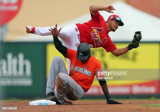 Lewis Brinson of the Miami Marlins upends second baseman Breyvic Valera of the St Louis Cardinals after being tagged out attempting to steal second...