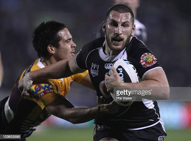 Lewis Brown of the Warriors fends off Corey Norman of the Broncos to score a try during the round 25 NRL match between the Warriors and the Brisbane...