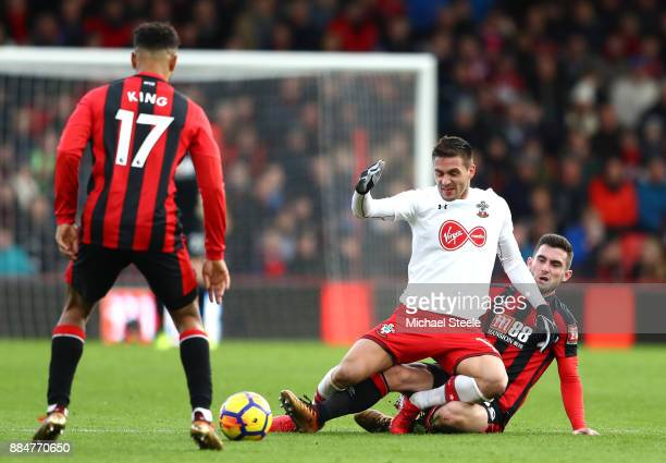 Lewis Cook of AFC Bournemouth tackles Dusan Tadic of Southampton during the Premier League match between AFC Bournemouth and Southampton at Vitality...
