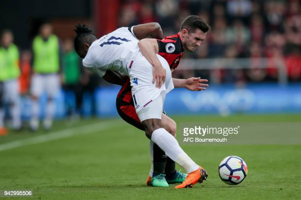 Lewis Cook of Bournemouth and Wilfried Zaha of Crystal Palace get themselves in a tangle during the Premier League match between AFC Bournemouth and...