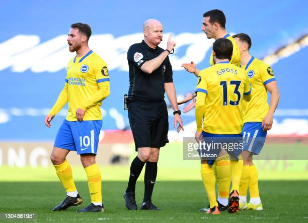 Lewis Dunk and Pascal Gross of Brighton and Hove Albion confront referee Lee Mason as he makes changes to his decision to disallow, then allow, then...
