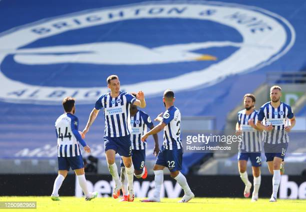 Lewis Dunk of Brighton and Hove Albion celebrates with Aaron Connolly and Martin Montoya after scoring his team's first goal during the Premier...