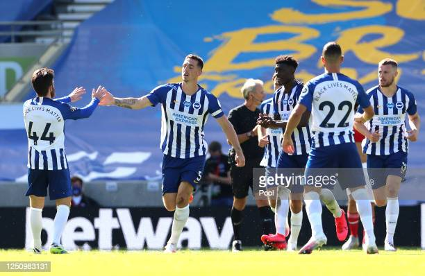Lewis Dunk of Brighton and Hove Albion celebrates with Aaron Connolly after scoring his team's first goal during the Premier League match between...