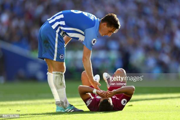 Lewis Dunk of Brighton and Hove Albion checks if Sergio Aguero of Manchester City is okay after a challenge during the Premier League match between...