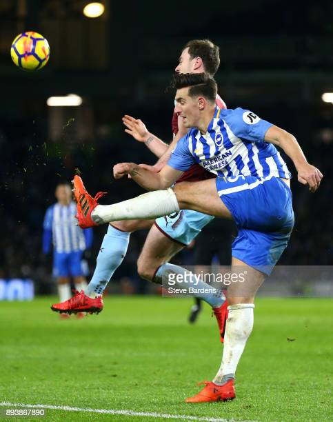 Lewis Dunk of Brighton and Hove Albion clears the ball while under pressure from Ashley Barnes of Burnley during the Premier League match between...