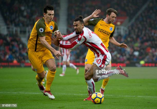 Lewis Dunk of Brighton and Hove Albion is challenged by Maxim ChoupoMoting of Stoke City during the Premier League match between Stoke City and...