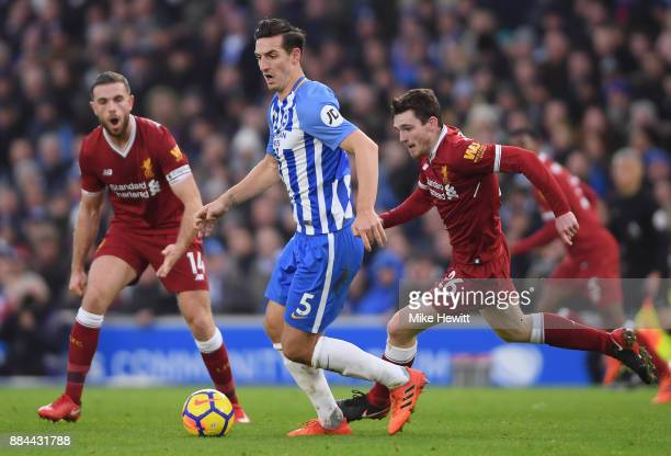 Lewis Dunk of Brighton and Hove Albion is put under pressure by Andy Robertson of Liverpool during the Premier League match between Brighton and Hove...