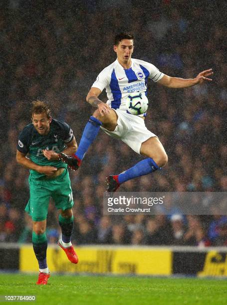 Lewis Dunk of Brighton and Hove Albion jumps for the ball under pressure from Harry Kane of Tottenham Hotspur during the Premier League match between...