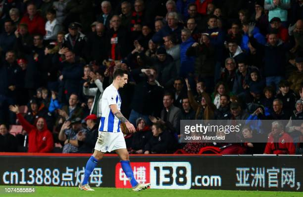 Lewis Dunk of Brighton and Hove Albion leaves the pitch after being sent off by referee Mike Dean during the Premier League match between AFC...