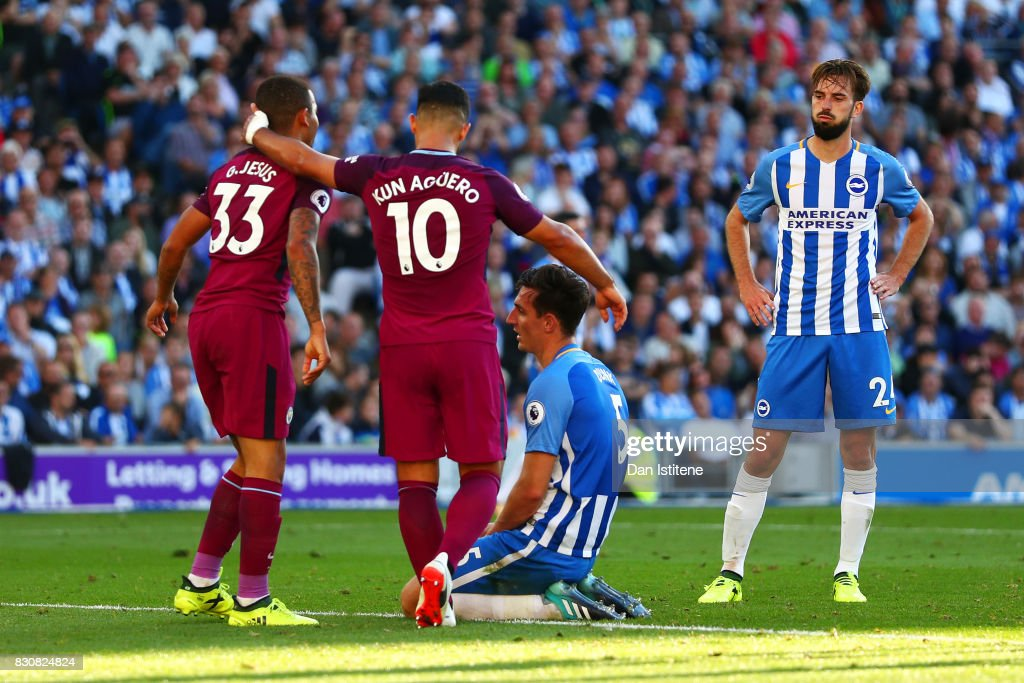 Lewis Dunk of Brighton and Hove Albion shows his dejection after scoring an own goal as Sergio Aguero and Gabriel Jesus of Manchester City celebrate during the Premier League match between Brighton and Hove Albion and Manchester City at Amex Stadium on August 12, 2017 in Brighton, England.