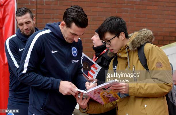 Lewis Dunk of Brighton and Hove Albion signs autographs as he arrives at the stadium prior to the Premier League match between Stoke City and...