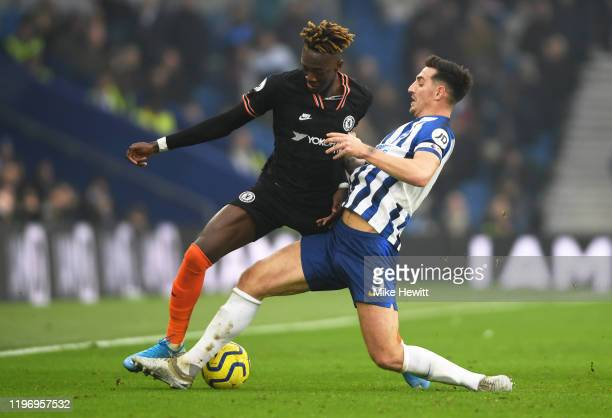 Lewis Dunk of Brighton and Hove Albion tackles Tammy Abraham of Chelsea during the Premier League match between Brighton Hove Albion and Chelsea FC...