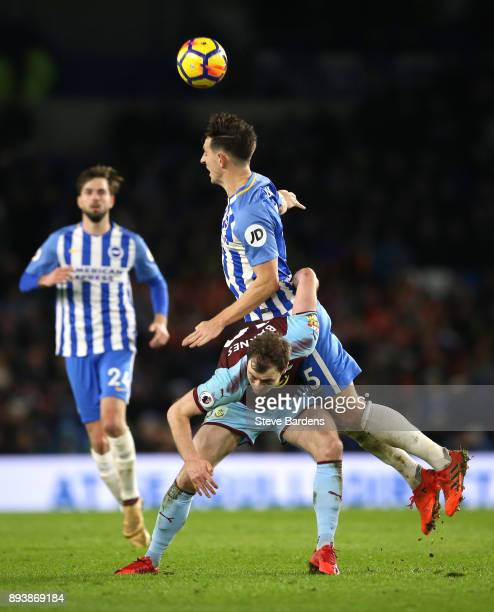 Lewis Dunk of Brighton and Hove Albion wins a header over Ashley Barnes of Burnley during the Premier League match between Brighton and Hove Albion...
