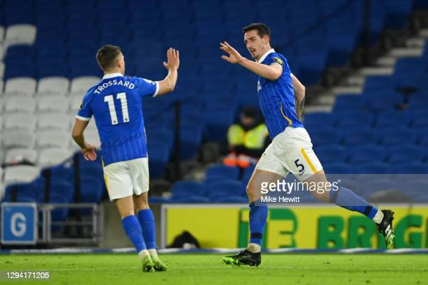 Lewis Dunk of Brighton & Hove Albion celebrates with teammate Leandro Trossard after scoring their team's third goal during the Premier League match...