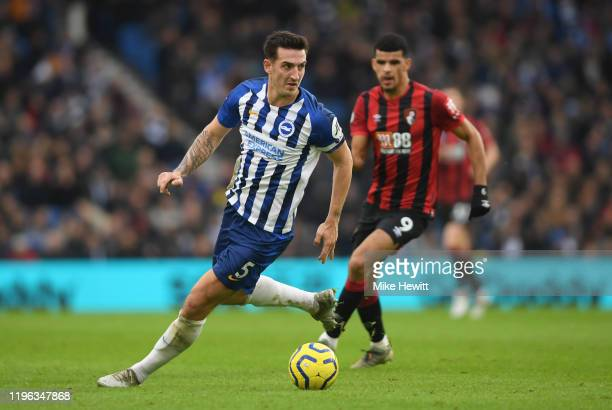 Lewis Dunk of Brighton & Hove Albion runs with the ball as Dominic Solanke looks on during the Premier League match between Brighton & Hove Albion...