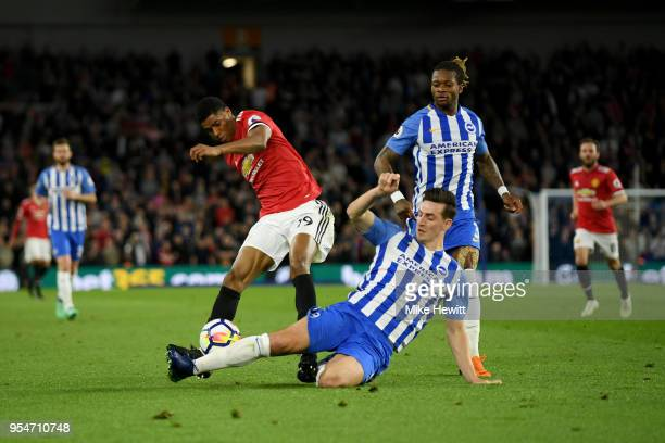 Lewis Dunk of Brighton Hove Albion slides in to tackle Marcus Rashford of Manchester United during the Premier League match between Brighton and Hove...