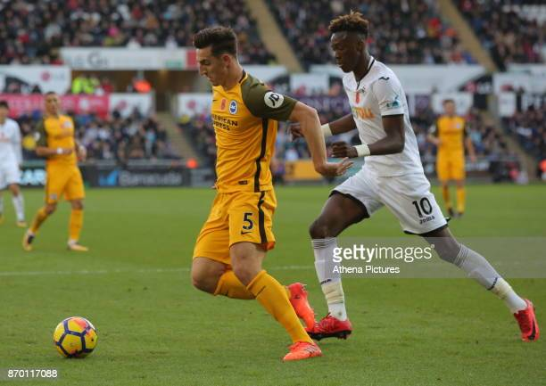 Lewis Dunk of Brighton is chased by Tammy Abraham of Swansea City during the Premier League match between Swansea City and Brighton and Hove Albion...