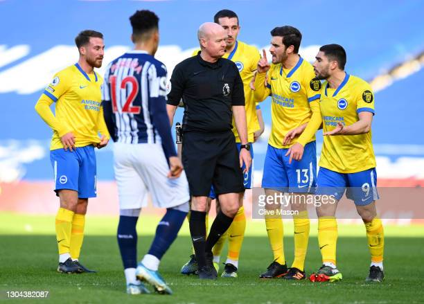 Lewis Dunk, Pascal Gross and Neal Maupay of Brighton and Hove Albion confront referee Lee Mason as he makes changes to his decision to disallow, then...