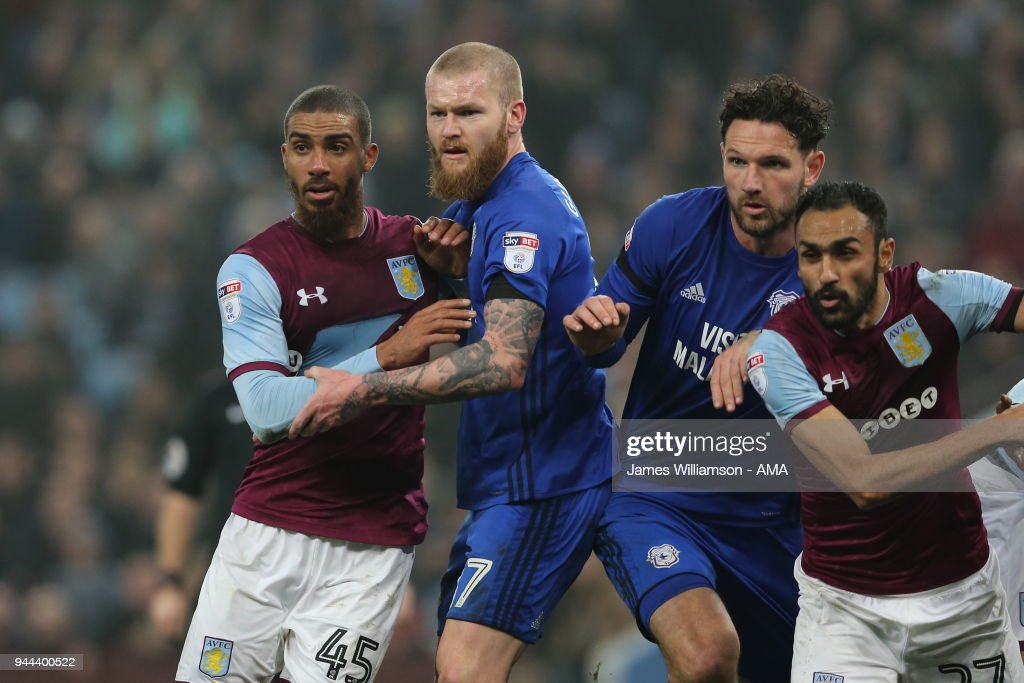 Lewis Grabban of Aston Villa wearing a ripped shirt battling with Aron Gunnarsson of Cardiff City during the Premier League match between Leicester City and Newcastle United at The King Power Stadium on April 7, 2018 in Leicester, England.