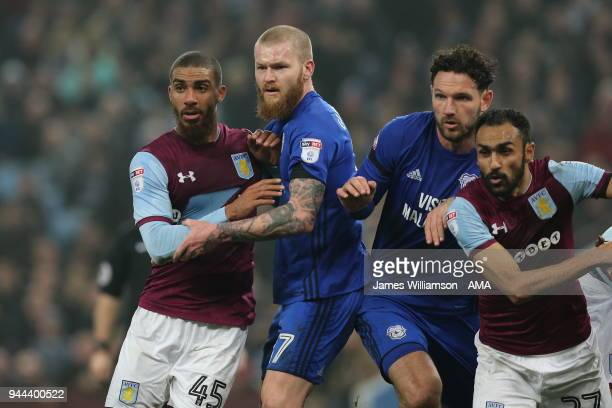 Lewis Grabban of Aston Villa wearing a ripped shirt battling with Aron Gunnarsson of Cardiff City during the Premier League match between Leicester...