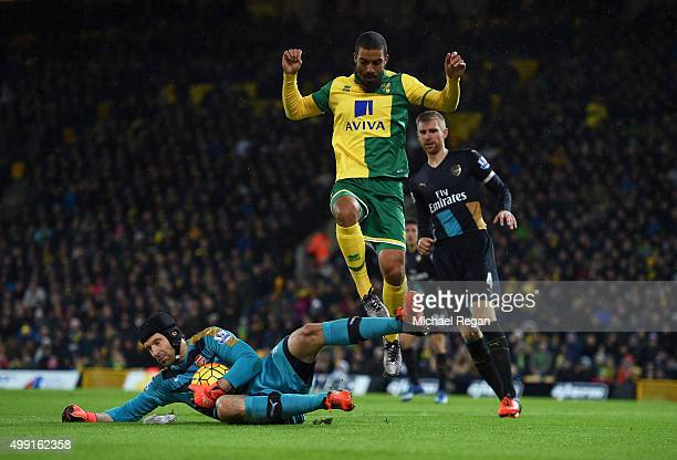 Lewis Grabban of Norwich City jumps over goalkeeper Petr Cech of Arsenal during the Barclays Premier League match between Norwich City and Arsenal at...