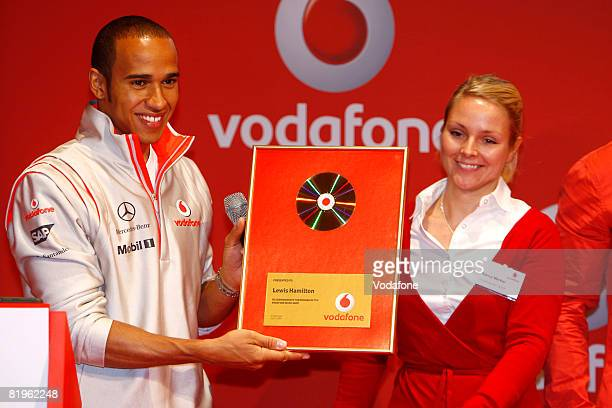 Lewis Hamilton is presented with a disc by Nancy Merker of Vodafone GmbH after competing against Heikki Kovalainen of the Vodafone McLaren Mercedes...