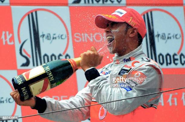 Lewis Hamilton of Britain celebrates by spraying champagne on himself on the winners podium after driving his McLaren Mercedes to victory in the...