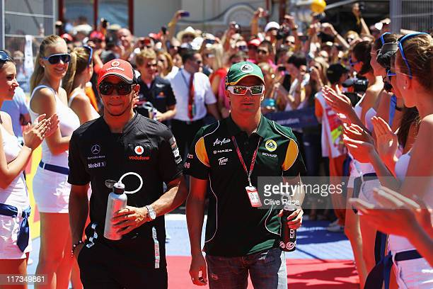 Lewis Hamilton of Great Britain and McLaren and Heikki Kovalainen of Finland and Team Lotus makes their way to the drivers parade before the European...