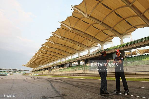 Lewis Hamilton of Great Britain and McLaren and his father Anthony Hamilton talk on the main straight following qualifying for the Malaysian Formula...
