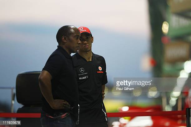 Lewis Hamilton of Great Britain and McLaren and his father Anthony Hamilton talk outside the McLaren team garage following qualifying for the...
