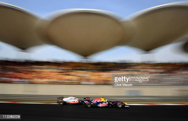 Lewis Hamilton of Great Britain and McLaren and Sebastian Vettel of Germany and Red Bull Racing drive side by side into the hairpin during the...