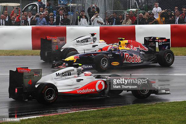 Lewis Hamilton of Great Britain and McLaren and team mate Jenson Button of Great Britain and McLaren drive either side of Mark Webber of Australia...