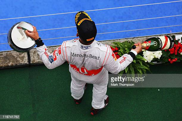 Lewis Hamilton of Great Britain and McLaren celebrates on the podium after winning the German Formula One Grand Prix at the Nurburgring on July 24,...