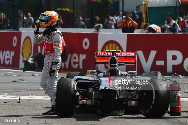 Lewis Hamilton of Great Britain and McLaren gestures to Romain Grosjean of France and Lotus after they crash out at the first corner at the start of...