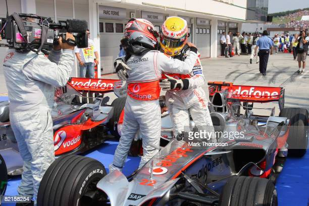 Lewis Hamilton of Great Britain and McLaren Mercedces celebrates in parc ferme with team mate Heikki Kovalainen of Finland after claiming pole...