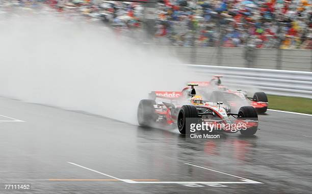 Lewis Hamilton of Great Britain and McLaren Mercedes and Fernando Alonso of Spain and McLaren Mercedes drive through the wet conditions during the...