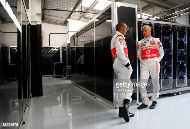 Lewis Hamilton of Great Britain and McLaren Mercedes and Heikki Kovalainen of Finland and McLaren Mercedes are seen in their team garage during...