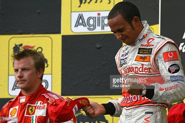 Lewis Hamilton of Great Britain and McLaren Mercedes and Kimi Raikkonen of Finland and Ferrari celebrate on the podium after the Hungarian Formula...