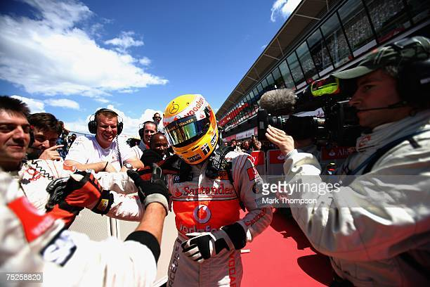 Lewis Hamilton of Great Britain and McLaren Mercedes celebrates with his team after taking pole position in qualifying for the British Formula One...