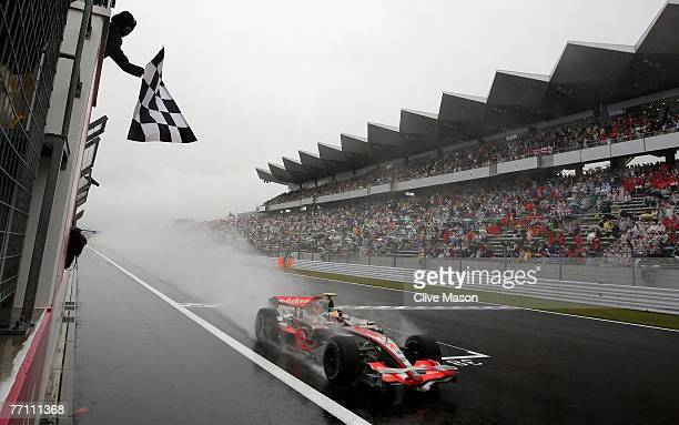 Lewis Hamilton of Great Britain and McLaren Mercedes crosses the finish line to win the Japanese Formula One Grand Prix at the Fuji Speedway on...