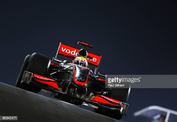 Lewis Hamilton of Great Britain and McLaren Mercedes exits the pitlane at dusk during practice for the Abu Dhabi Formula One Grand Prix at the Yas...