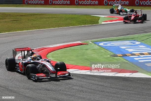 Lewis Hamilton of Great Britain and McLaren Mercedes leads from Kimi Raikkonen of Finland and Ferrari and Adrian Sutil of Germany and Force India at...