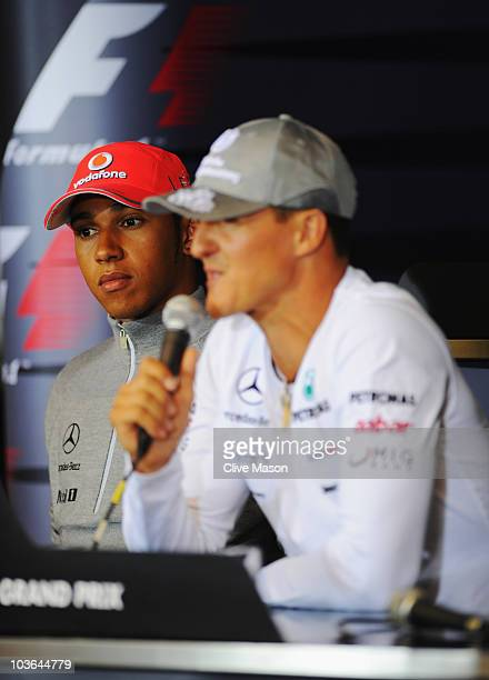 Lewis Hamilton of Great Britain and McLaren Mercedes listens to Michael Schumacher of Germany and Mercedes GP talks as they attend the drivers press...