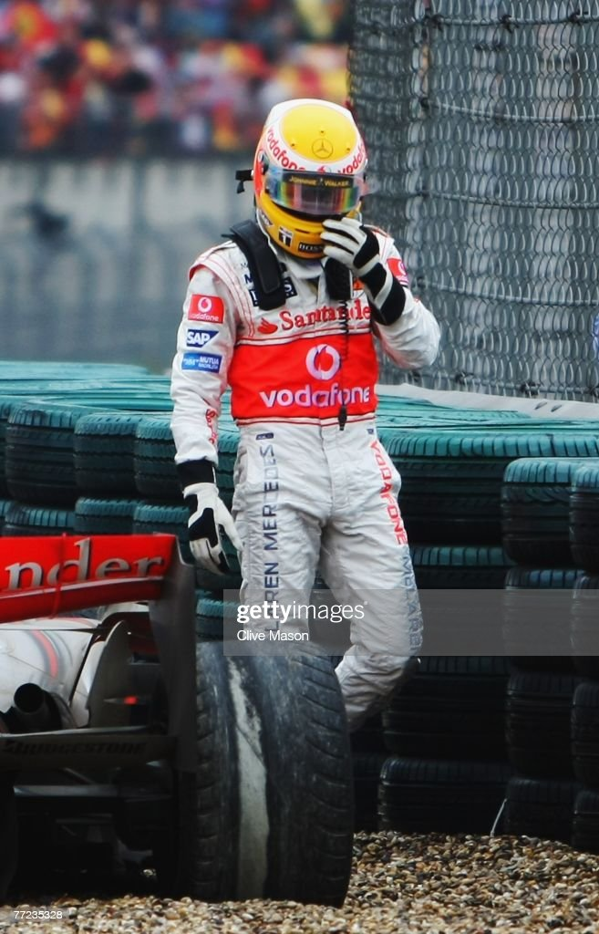 Lewis Hamilton of Great Britain and McLaren Mercedes looks at his worn rear tyre as he retires early from the Chinese Formula One Grand Prix at the Shanghai International Circuit on October 7, 2007 in Shanghai, China.