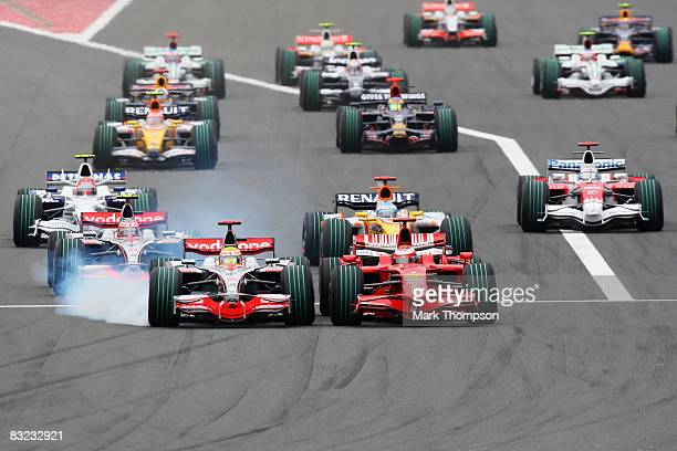 Lewis Hamilton of Great Britain and McLaren Mercedes outbreaks Kimi Raikkonen of Finland and Ferrari into the first corner at the start of the...