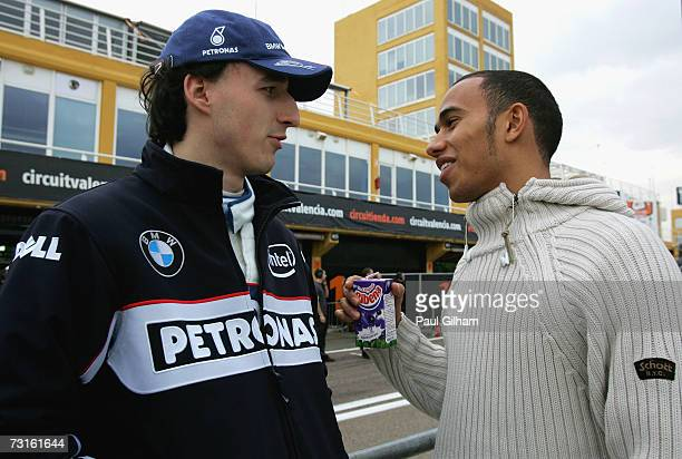 Lewis Hamilton of Great Britain and McLaren Mercedes talks to Robert Kubica of Poland and BMW Sauber on the pit wall during Formula One testing at...