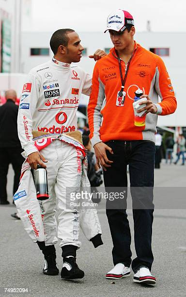 Lewis Hamilton of Great Britain and McLaren Mercedes talks with Adrian Sutil of Germany and Spyker F1 following practice for the French Formula One...