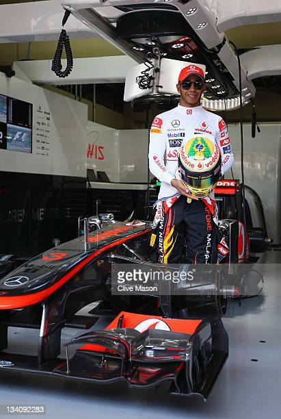 Lewis Hamilton of Great Britain and McLaren shows his specially designed drivers helmet featuring a tribute to the late Ayrton Senna during practice...